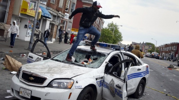 Demonstrators jump on a damaged Baltimore police department vehicle during clashes in Baltimore